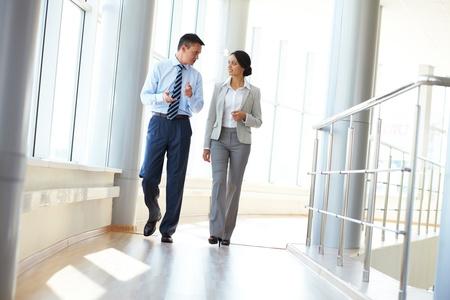 Vertrouwen in business partners die in kantoorgebouw lopen en bespreken van het werk