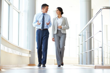 Confident business partners walking down in office building and discussing work
