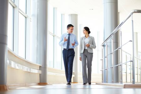 walking down: Confident business partners walking down in office building and talking