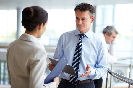 new strategy: Image of confident businessman looking at partner while discussing new strategy Stock Photo