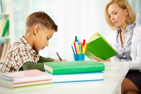 teaching crayons: Ritratto di ragazzo diligente scrivere qualcosa con la sua lettura tutore vicino