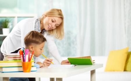 tutor: Retrato de tutor inteligente con lápiz corrigiendo errores en el cuaderno de pupil?s Foto de archivo