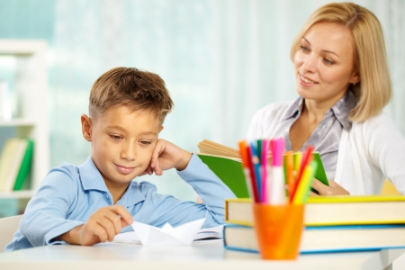 private schools: Portrait of handsome boy at workplace with his tutor sitting near by and looking at him Stock Photo