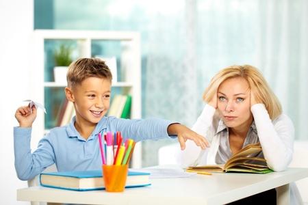 niños estudiando: Retrato de niño travieso jugando con avión de papel durante la lección y tutor molesta tocando su cabeza Foto de archivo