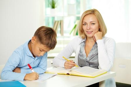 diligente: Retrato de tutor bonita mirando la c�mara con diligente alumno haciendo notas cerca