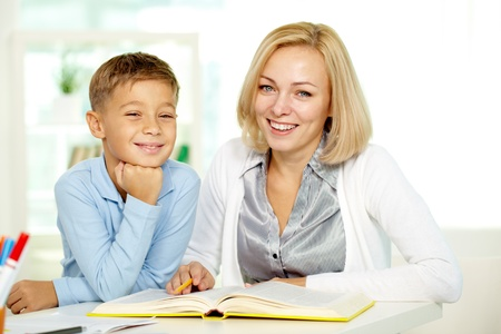 Portrait of pretty tutor and diligent pupil looking at camera with smiles photo
