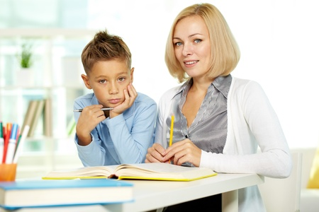 Portrait of pretty tutor and diligent pupil looking at camera photo