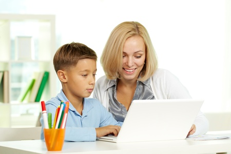 home school: Portrait of pretty tutor and her pupil working with laptop Stock Photo