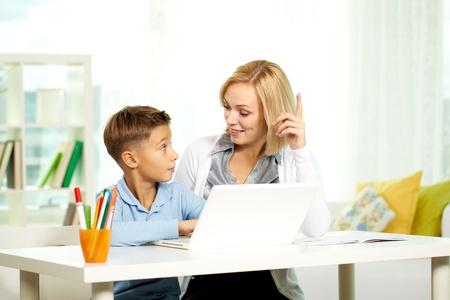 diligente: Retrato de Linda tutor y alumno diligente discutir ideas mientras se trabaja con equipos port�tiles Foto de archivo