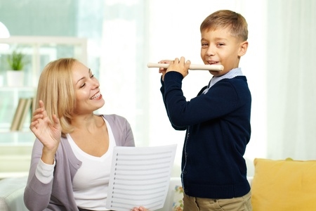 teaching music: Portrait of happy pupil playing the flute with tutor on background