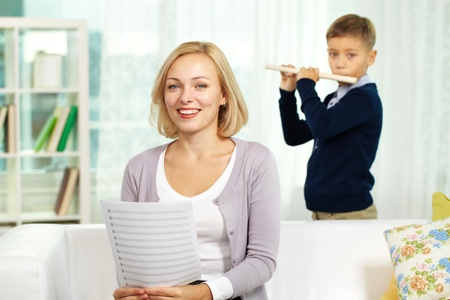 teaching music: Portrait of happy tutor with notes looking at camera on background of pupil playing the flute Stock Photo