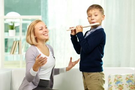 flute instrument: Portrait of handsome pupil playing the flute while happy tutor admiring his play