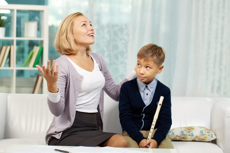 private schools: Portrait of pupil with the flute looking at his tutor speaking about music with admiration