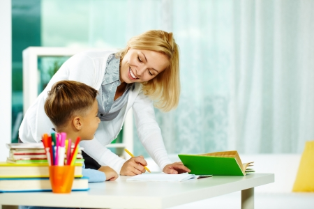 private school: Portrait of smart tutor with pencil correcting mistakes in pupil's notebook