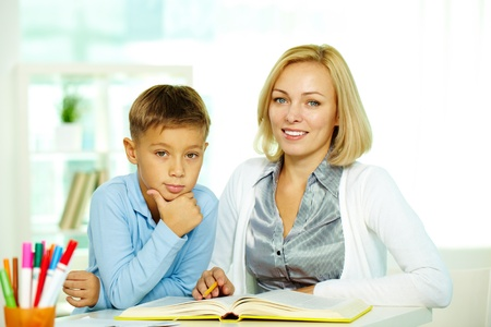 tutoring: Portrait of pretty tutor and diligent pupil looking at camera with smiles