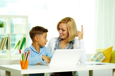 tutor: Retrato de Linda tutor y alumno diligente discutir ideas mientras se trabaja con equipos portátiles Foto de archivo