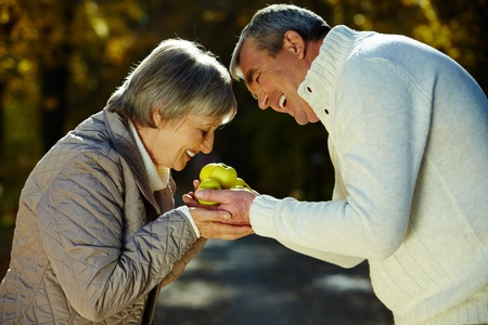 Photo of aged woman smelling apples in her husband hands in the park photo