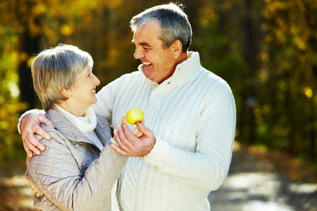 amorous woman: Photo of amorous aged man and woman holding apple and looking at each other