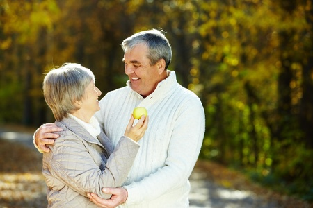 Photo of amorous aged man and woman holding apple and looking at each other photo
