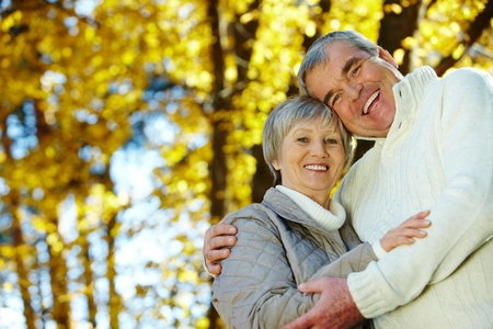 Photo of amorous aged man and woman looking at camera in autumnal park photo