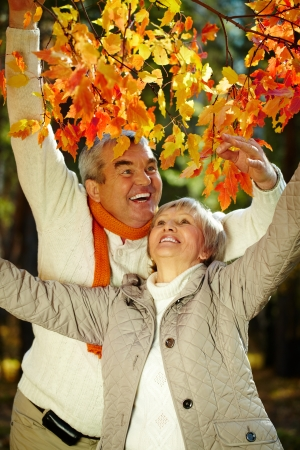female bonding: Photo of joyful man and woman looking at each other in autumnal park Stock Photo