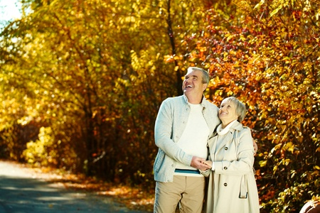 emotional couple: Photo of happy aged man and woman looking at something in autumnal park Stock Photo