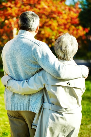 Backs of aged man and woman taking a walk in autumnal park photo