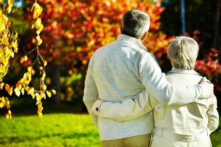 Rear view of aged man and woman taking a walk in autumnal park