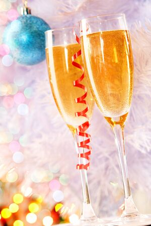 Two champagne flutes with firtree branch behind   photo