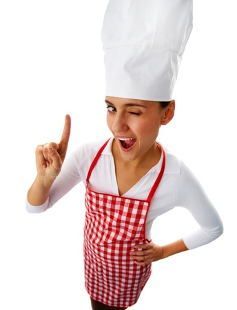 Portrait of happy female chef winking to you and keeping her forefinger raised photo