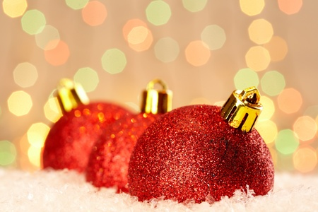 natale: Red glittering Christmas baubles against glaring background Stock Photo