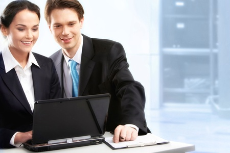 Creative image of two partners working with laptop in office photo