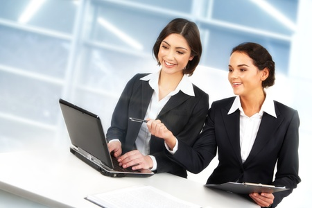 Creative image of two businesswomen working with laptop in office photo