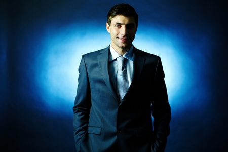 principal: Portrait of elegant businessman in suit looking at camera in darkness Stock Photo