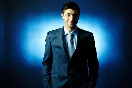 director de escuela: Retrato de hombre de negocios elegante en traje mirando a la cámara en la oscuridad