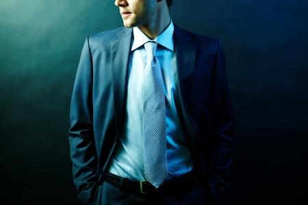 spokesperson: Figure of elegant businessman in suit posing in darkness Stock Photo