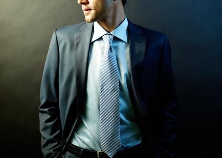traje: Figura del empresario elegante traje posando en la oscuridad Foto de archivo