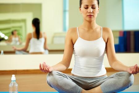 Portrait of serene girl doing yoga exercise in gym photo