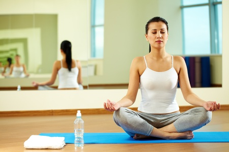 Portrait of serene girl doing yoga exercise in gym Stock Photo - 11064200