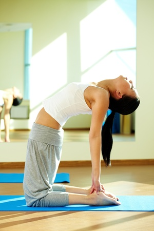 Portrait of young flexible girl doing physical exercise in gym photo