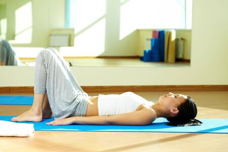 Portrait of serene girl doing yoga exercise in gym photo