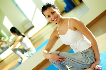 Portrait of happy sportive girl sitting on the floor of gym during training photo