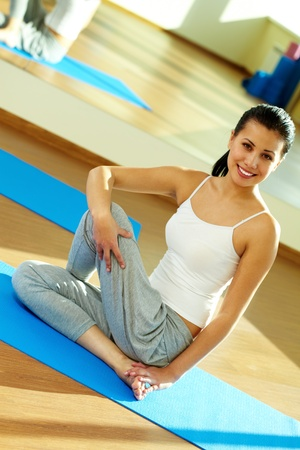Portrait of happy sportive girl sitting on the floor of gym during training Stock Photo - 11064195