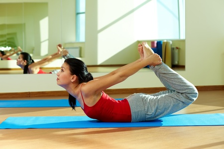 Portrait of young sporty girl doing stretching exercise photo