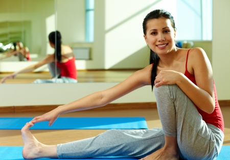 Portrait of young sporty girl looking at camera during workout in gym photo