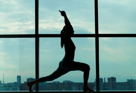 Silhouette of sporty girl doing physical exercise photo
