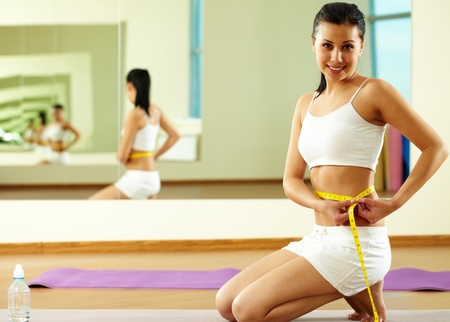 woman measuring waist: Portrait of happy fit female measuring her waist