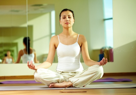 incienso: Retrato de niña serena haciendo ejercicios de yoga con el incensario humeante cerca Foto de archivo