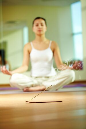 Close-up of smoking incense with serene girl doing yoga exercise on background photo