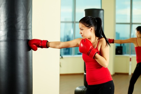 Portrait of young woman in red boxing gloves training in gym  photo